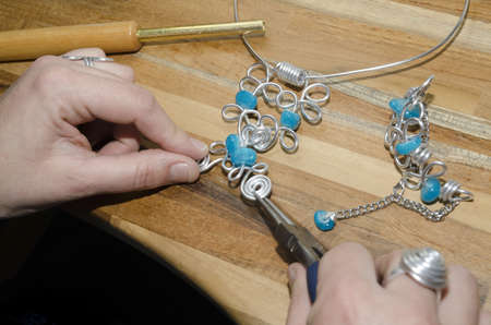 womans hands creating a fashion jewelery