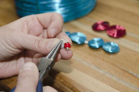 creador: manos de una mujer de moda la creación de joyas con perlas
