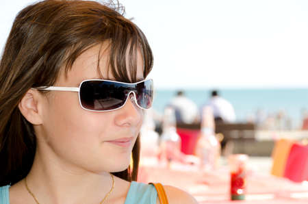 portrait of a girl with sunglasses on holiday at the beach