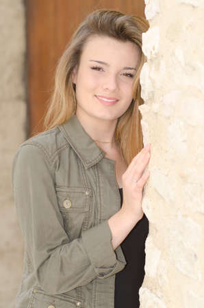 beautiful smiling girl against a stone wall Stock Photo