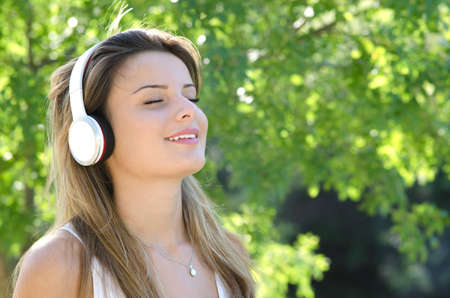 portrait on a smiling young girl listening to music with eyes closed Stock Photo