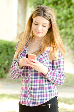 beautiful girl using a smartphone for social networking Stock Photo