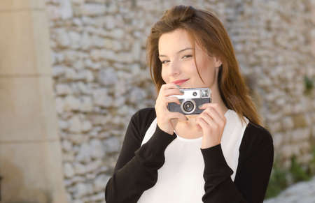 Pretty young girl holding an old camera and looking photographer Stock Photo