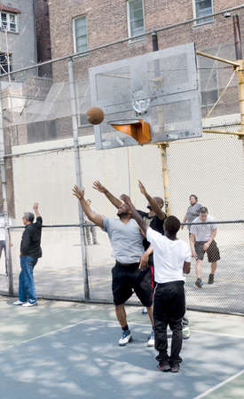 New-York City, USA - May 04, 2015: young men in action playing basketball in the street Editorial