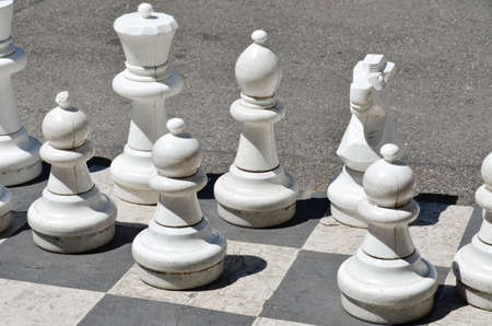 large white figurines of chess game on the asphalt