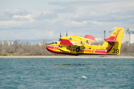 Marseille, France - March 30, 2015: Canadair water bomber plane in training in the harbor near a petrochemical industrial Site