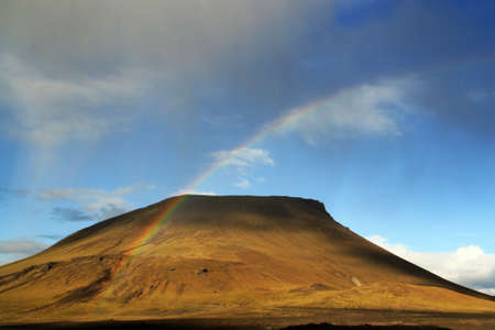 A naked hill with a small cloud raining and a rainbow.