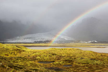 Beautiful double rainbow, glacier and lake in Iceland in a rainy day.