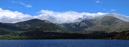 Natural landscape in Madrid, Spain. Mountains, lake, forest, clouds and blue sky.