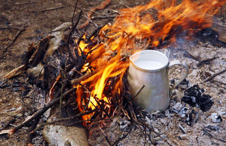 Jug of milk with soluble coffee on a campfire.