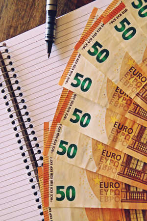 Banknotes of 50 euros and a notebook. Stok Fotoğraf