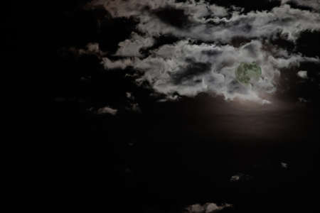 Night sky where the full moon hides among the clouds. Banco de Imagens