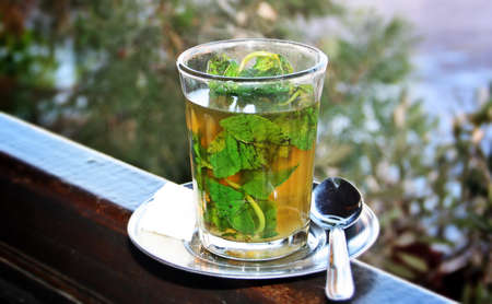 A glass of moruno tea with mint leaves served in a terrace of a restaurant in Marrakech (Morocco).