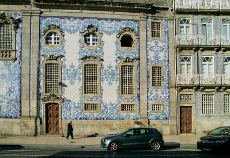 An old man walking on the Carlos Alberto square sidewalk. The traditional blue and white tiles (portuguese: azulejo) of the wall of Carmo church at the background (Porto, Portugal).