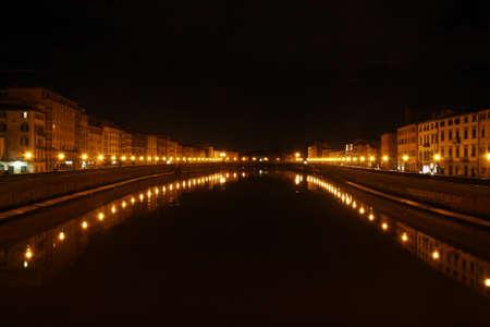 The Arno river as it passes through Pisa (Italy) illuminated at night.