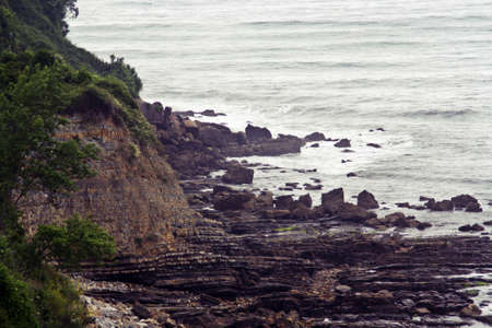 Rocky Cliff with stratified rocks in a beach from the north of Spain. La Griega beach.