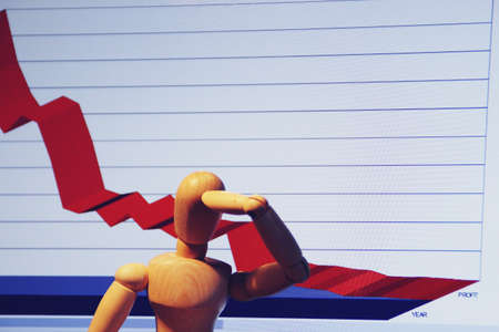 Wooden human mannequin putting his hand on his head with a graph of economic losses. Stok Fotoğraf