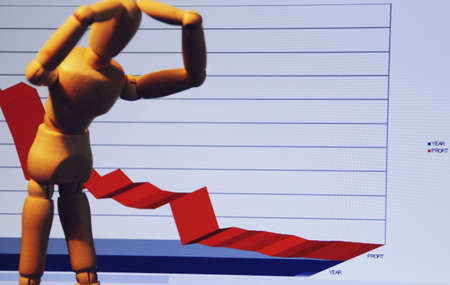 Wooden human mannequin putting his hands on his head with a graph of economic losses.
