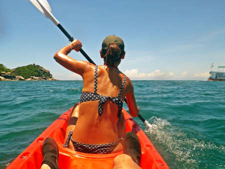 Young girl paddling a kayak in a tropical ocean in summer. Exploring the coastline of the island of Koh Tao by kayak, Gulf of Thailand, Thailand.