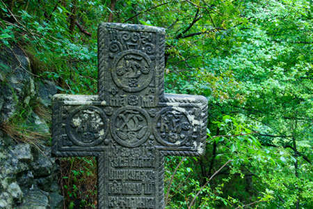 Cross next to the Chapel of the Heart of Queen Mary. Stone Christian cross with religious motifs located near Bran Castle in Romania.