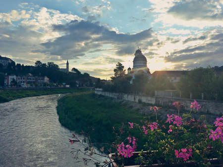 Sunset over the Tarnava River in Sighisoara, Romania. A nice view of the river with the Church of the Holy Trinity to the right, just as the sun sets.