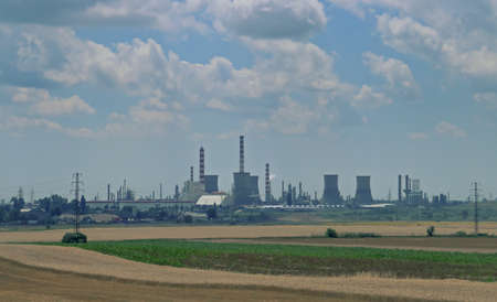 Chimneys, cooling towers and other industrial facilities in the southeastern part of Romania. Facilities between the fields of cereal crops seen from the DN2A road.