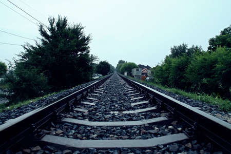 Close-up of a train track on a rainy day. An old train track that runs through vegetation and heads straight for the horizon on a dark rainy day next to Olimp in Romania.