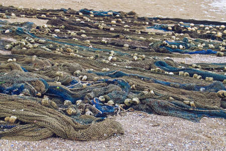 Fishing nets spread out on the sand on the beach. Traditional fishing nets drying in the open air on the beach of Olimp, Romania. Imagens