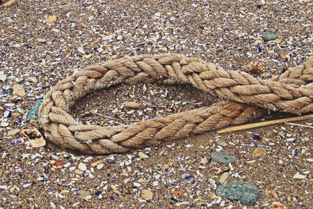 An old rope on the sand. Close-up of an old dirty and weathered rope.