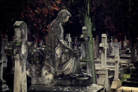 An old statue in a tomb of a catholic cemetery in Madrid, Spain. Weathered statue with lichens due to having been exposed to atmospheric conditions.