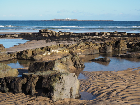 Rocky shore and rock pools with a view of the Farne Islands at Bamburgh, Northumberland, England