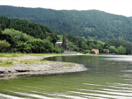 Furnas lake shore with a church and woodland, Sao Miguel, The Azores