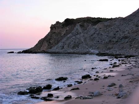 Headland on the Algarve coast, Portugal, at dusk with a purple glow