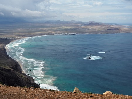 View over Playa de Famara with black volcanic cliffs, rocks and waves, Lanzarote