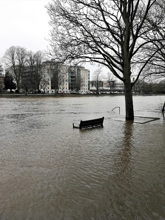 Park bench surrounded by flood water from the River Ouse in York, England