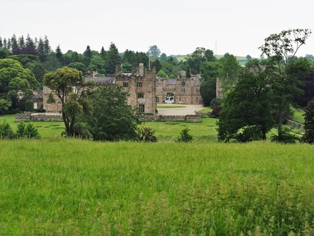 View of Ripley Castle, North Yorkshire, across green meadows