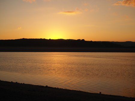 Beautiful glow as the sun sets behind the Cumbrian hills across the Kent River estuary at Arnside
