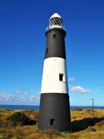 Lighthouse at Spurn Point nature reserve, East Yorkshire, England, against a blue sky