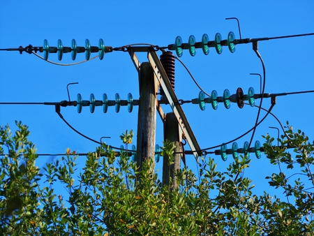 Electrical power lines with blue glass insulators above a hedge with a clear blue sky Stock Photo