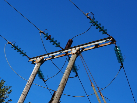 Electrical power lines with glass insulators against a clear blue sky
