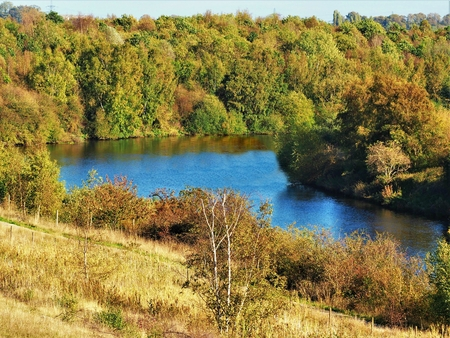 Rive Aire lined by autumn trees seen from Fairburn Ings nature reserve, Yorkshire, England Stock Photo
