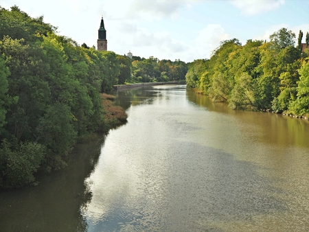 Wooded banks of the River Aura in Turku, Finland, with a view of the Cathedral tower above the trees