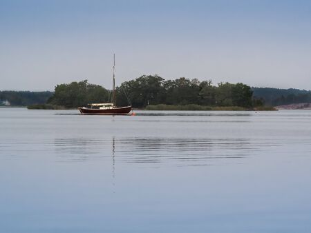 Sailing boat peacefully anchored in the calm Baltic Sea near Godby, Aland, Finland