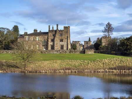 View of Ripley Castle from across the lake in the surrounding parkland, North Yorkshire, England