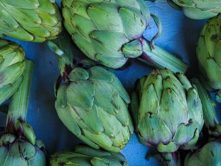 Display of green globe artichokes arranged on a blue background
