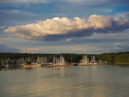 Light shining on the masts of sailing boats in a marina in the Turku Achipelago, Finland, with a dramati sky Фото со стока