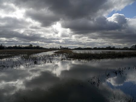 Dramatic cloudy sky over the flooded wetlands at Wheldrake Ings Nature Reserve, North Yorkshire, England Фото со стока