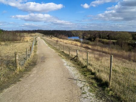 Path through Fairburn Ings Nature Reserve, West Yorkshire, England, with a view of the River Aire Фото со стока