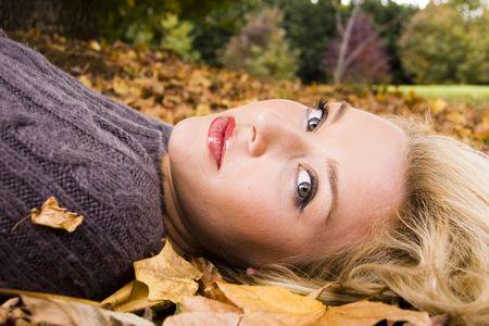 beautiful girl lying in the autumn leaves photo
