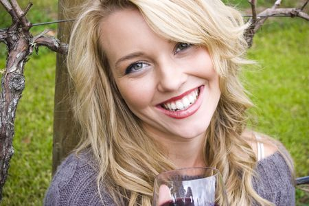 Beautiful girl drinking wine in a vineyard Stock Photo